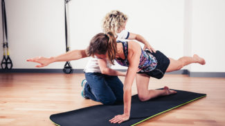 Person teaching Pilates to someone kneeling on an exercise mat