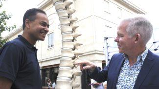 Dr Sengupta and Professor Gaffney smiling next to a model of a spine