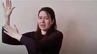Photo of Zoë Clark with her arm up to demonstrate a shoulder stretch