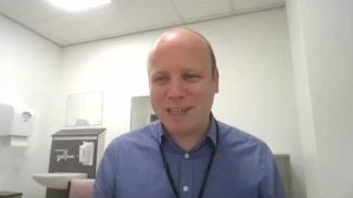 Photo taken of physiotherapist Will Gregory in his consultation room while speaking about virtual consultations