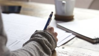 Image shows someone writing at a table with a mug nearby