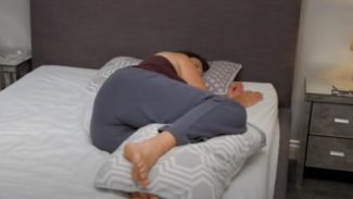Person lying on their side in bed with a pillow between their knees