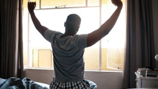 Person sat on a bed facing a sunny window, stretching their arms up