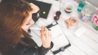 Woman sat at a desk thinking