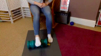 Person sat on a chair with foot on a foam roller