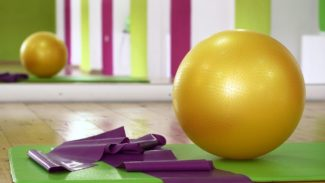 Photo of an exercise mat, resistance band and exercise ball