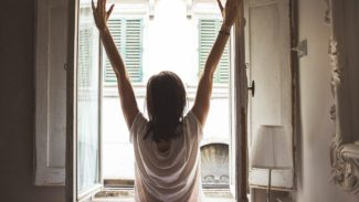 Image of a woman stood facing an open window and stretching her arms up
