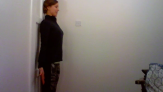 Photo of Emily Clarke standing with her back against the wall, demonstrating a posture exercise