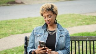 Image of a woman sat on a bench near grass, while reading from her phone