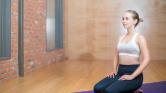 Woman kneeling on yoga mat and smiling