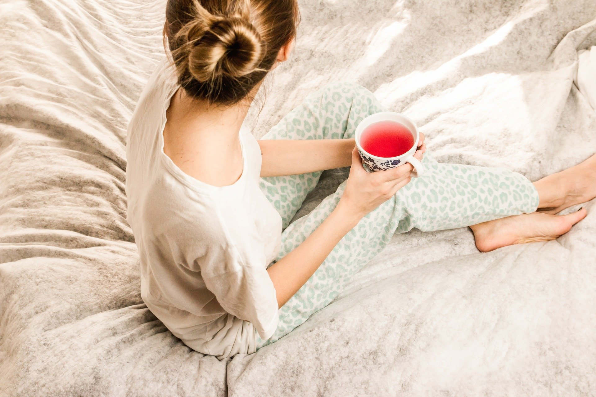 woman sat on bed holding a mug while looking away from the camera