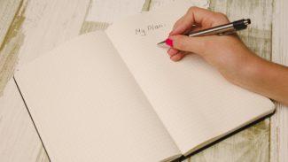 A hand writing in an open notebook