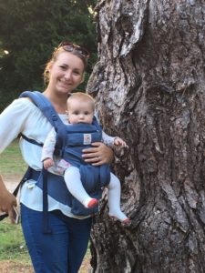 Jess with her baby in a carrier, in front of a tree