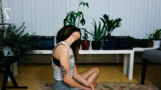Brown haired woman sat cross legged on the floor and tilting her head to the left to stretch her neck