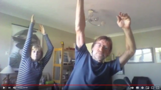 Screenshot of zoom video showing Ian and Andrea reaching their arms up and leaning to their left