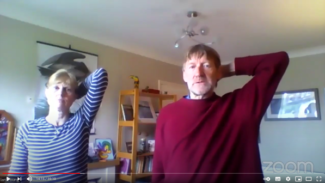 Screenshot of zoom video showing Ian and Andrea reaching their arm behind their head