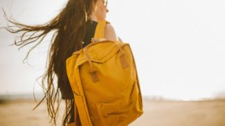 Woman with brown hair and glasses wearing a yellow backpack looks away from the camera