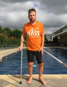 Darren Fletcher lives with axial SpA. He is wearing a NASS t-shirt and standing by the pool