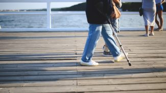 Man walking along a pier using a walking stick with the sea in the distance