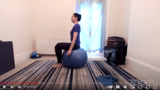Side view of Ruth sitting on an exercise ball with her arms resting beside her